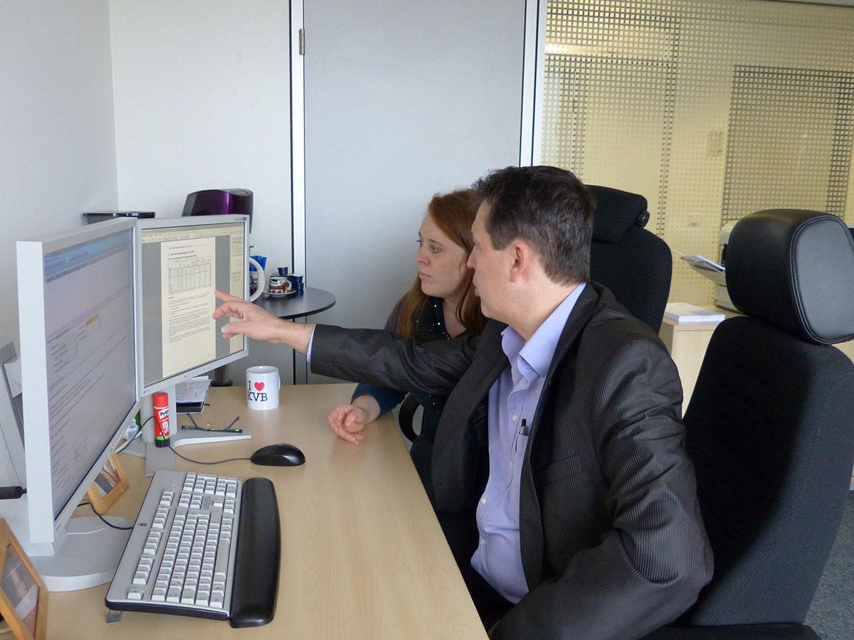 Michael erklärt mir, welche Rolle das VBM innerhalb des Qualitätsberichts einnimmt. Michael und Regina sitzen vorm PC und diskutieren den Qualitätsbericht.