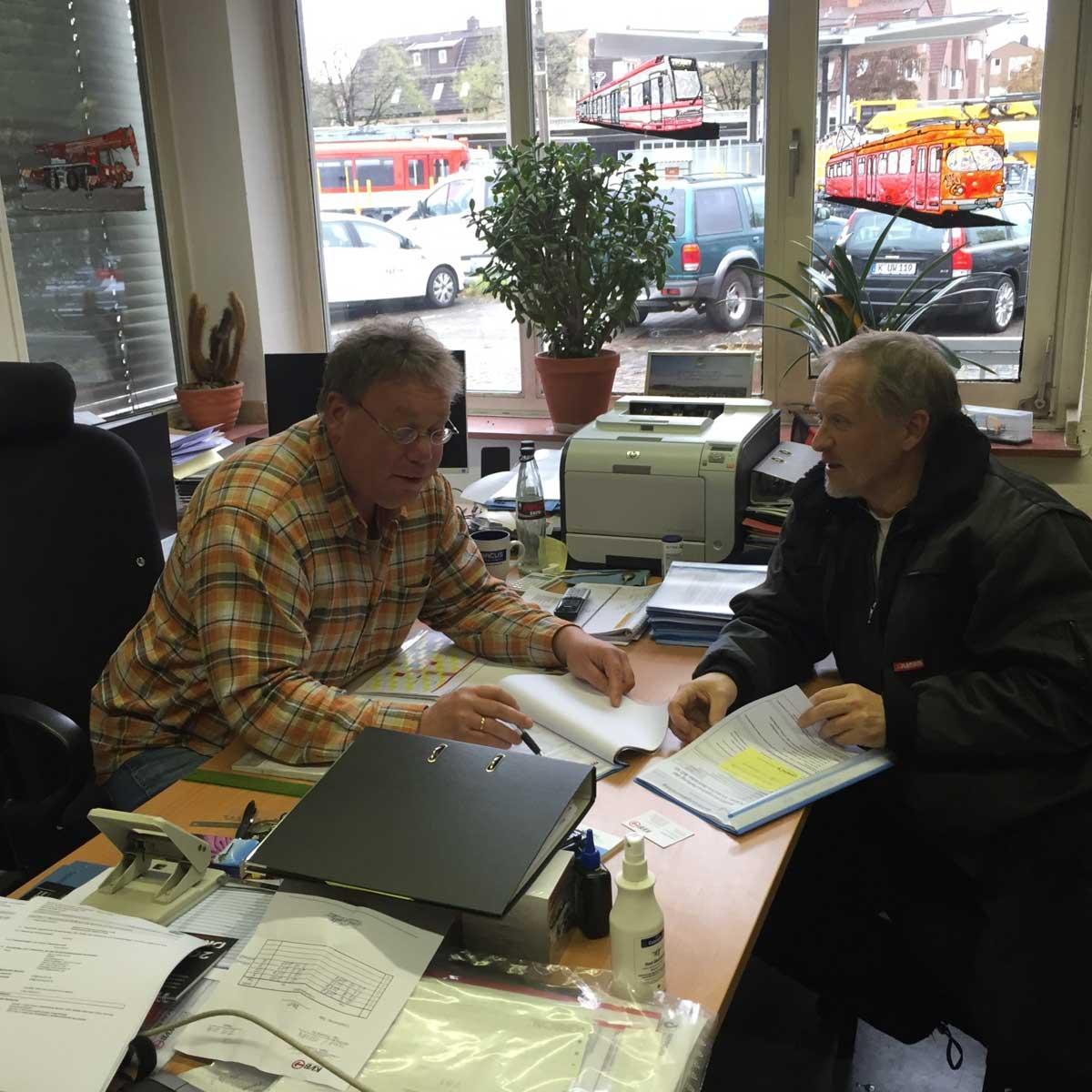 Dienstellenleiter Stefan und Vorarbeiter Dirk bei einer Arbeitsbesprechung im Büro.
