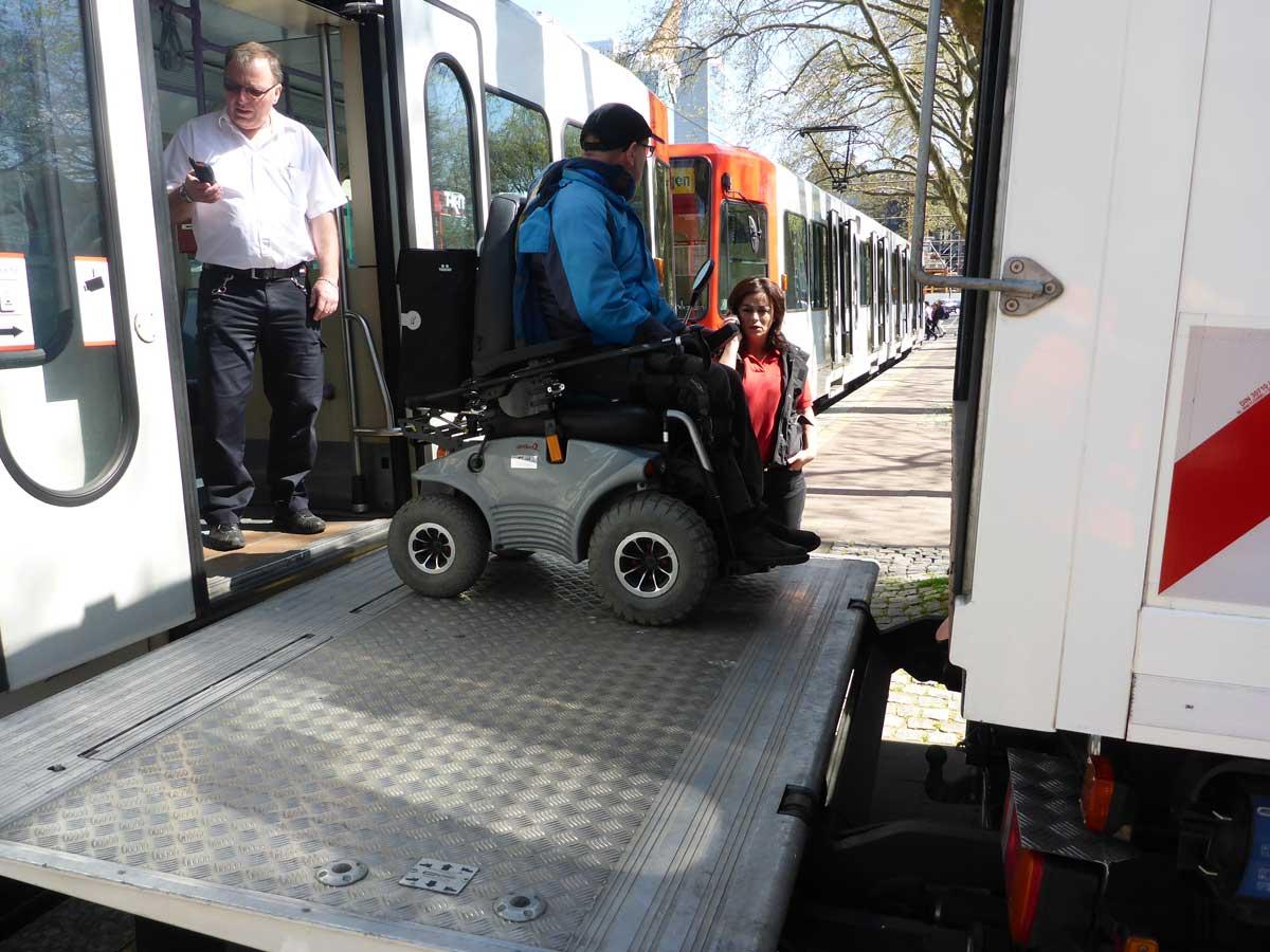 Der Tünnes 54 hilft einem mobilitätseingeschränkten Fahrgast mittels Hebebühne aus der Bahn.