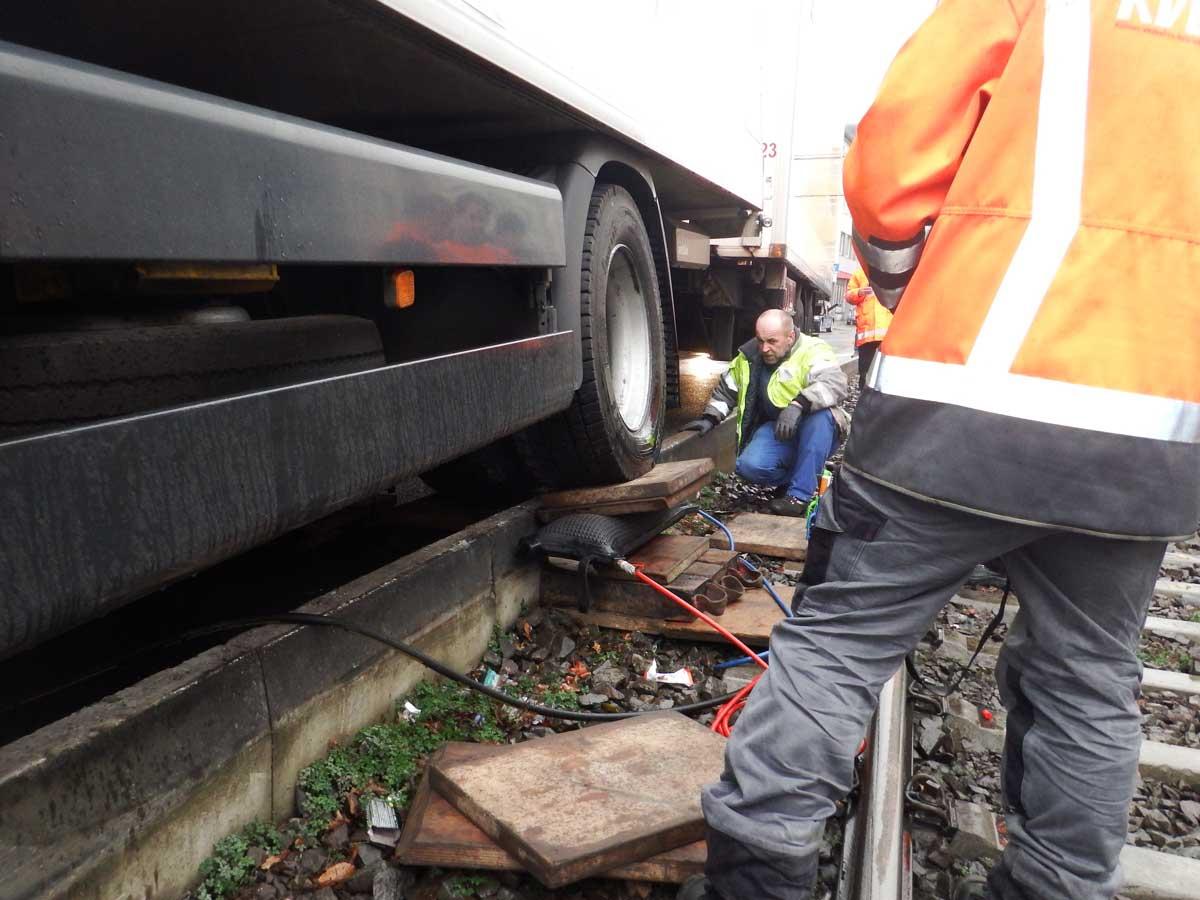 LKW im Gleis: Das Fahrzeug wird mit Hilfe pneumatischer Hebekissen und Holzbohlen aufgebockt.