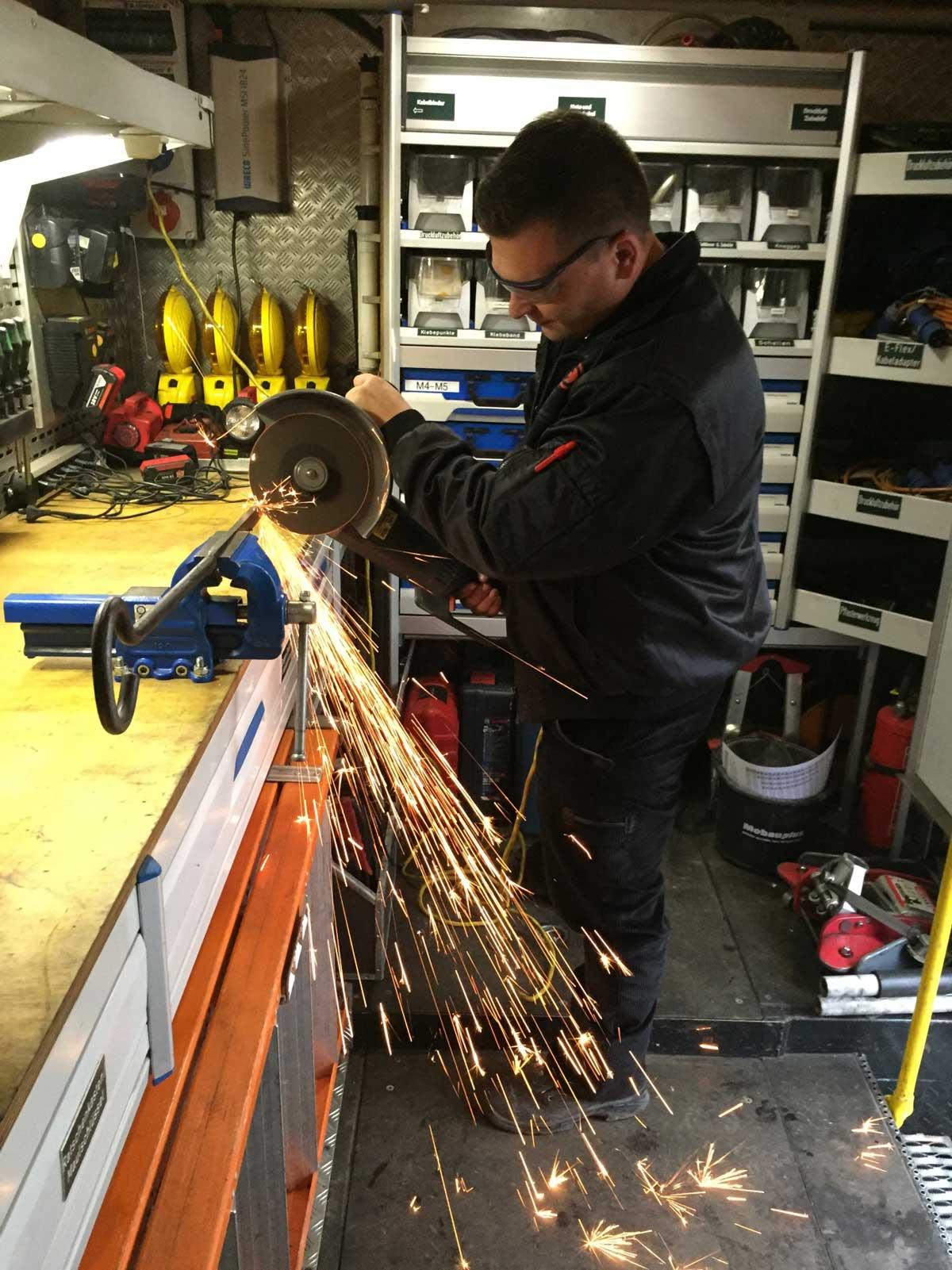 Industriemechaniker Dimitri an der Werkbank beim Zuschneiden eines Weichenstelleisens mit dem Winkelschleifer.