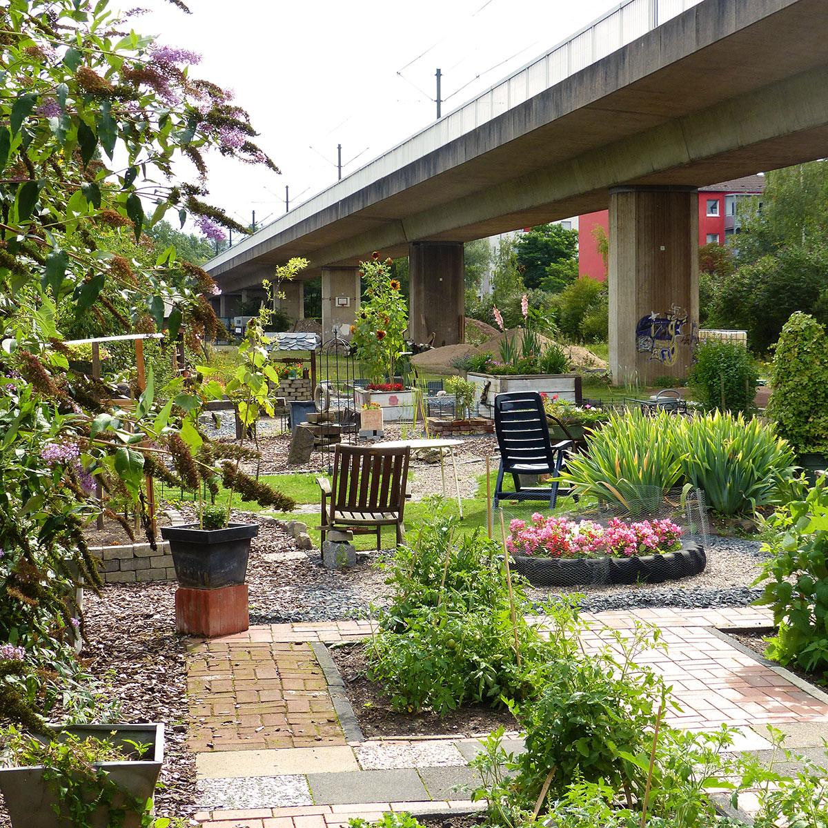 … und ein idyllischer Garten verschönern das Betongrau entlang der Hochbahn.