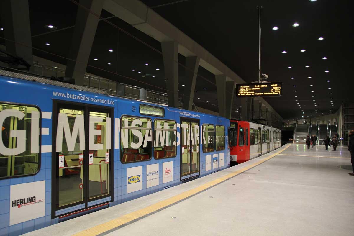 """Auf zwei Stadtbahnfahrzeugen warben die Unternehmen des Forums Butzweilerhof für den Standort im Kölner Westen (hier 2012 an der Haltestelle """"Breslauer Platz/Hauptbahnhof"""" …"""