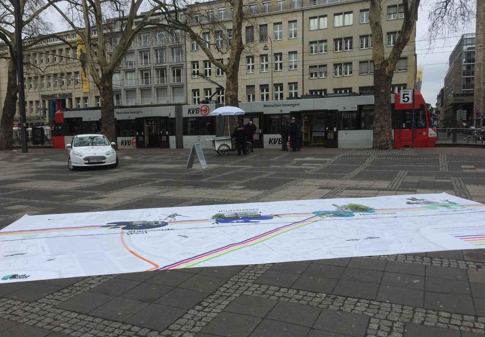 Infostadtbahn und ein großer Teppich mit dem Streckenverlauf auf dem Neumarkt.